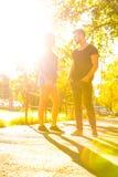 Jeunes couples parlant dans le coucher du soleil dans un milieu urbain Photos stock