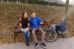 Jeunes couples parlant ensemble sur le banc en parc Photos stock