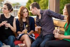 Jeunes couples parlant et flirtant Photographie stock libre de droits