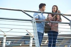 Jeunes couples parlant sur le pont dans l'environnement urbain tenant le traiteur Photos stock