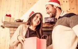 Jeunes couples partageant des cadeaux de Noël Photos stock