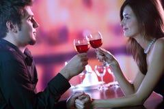 Jeunes couples partageant une glace de vin rouge dans le restaurant, celebrat Image stock
