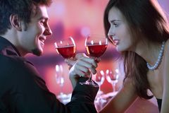 Jeunes couples partageant une glace de vin rouge dans le restaurant, celebrat Photos libres de droits