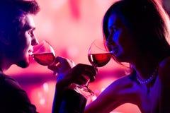Jeunes couples partageant une glace de vin rouge dans le restaurant, celebrat Photographie stock