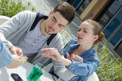 Jeunes couples payant des boissons à la terrasse de barre Photographie stock
