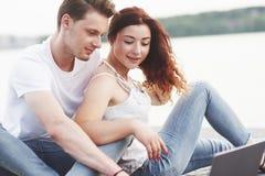 Jeunes couples pendant l'été pour un ordinateur portable en parc image stock