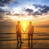 Jeunes couples pendant la lune de miel sur une plage tropicale, se tenant dans la lueur d'un coucher du soleil étonnant Amour Images stock