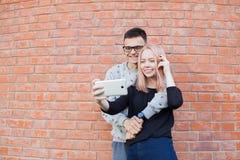 Jeunes couples photographiant un selfie avec le smartphone sur le fond du mur de briques rouge Photographie stock