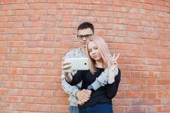 Jeunes couples photographiant un selfie avec le smartphone sur le fond du mur de briques rouge Fille blonde avec des yeux bleus e Images stock