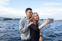 Jeunes couples photographiant un selfie avec le smartphone sur le fond du paysage urbain Remblai de rivière dans le saint Images libres de droits