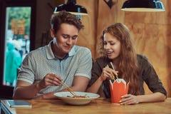 Jeunes couples portant les vêtements sport mangeant les nouilles épicées dans un restaurant asiatique Photographie stock libre de droits