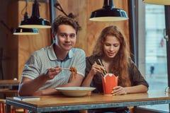 Jeunes couples portant les vêtements sport mangeant les nouilles épicées dans un restaurant asiatique Images stock