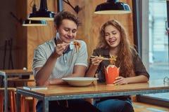Jeunes couples portant les vêtements sport mangeant les nouilles épicées dans un restaurant asiatique Image stock