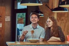 Jeunes couples portant les vêtements sport mangeant les nouilles épicées dans un restaurant asiatique Photo stock