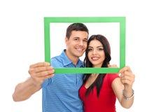 Jeunes couples posant derrière un cadre de tableau vert Images stock