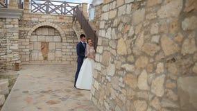 Jeunes couples posant pour une photo près d'un beau château et le mur en pierre avec un escalier en pierre banque de vidéos