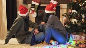 Jeunes couples positifs dans des chapeaux de Santa se reposant dans la chambre à l'arbre de Noël sur le plancher tournant à parti banque de vidéos