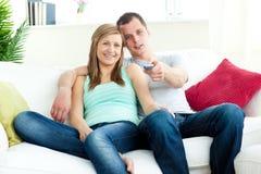 Jeunes couples positifs regardant la TV sur le sofa Photo stock