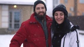Jeunes couples positifs riant dans l'arrière-cour devant la grande maison sous la neige en baisse Homme barbu et banque de vidéos
