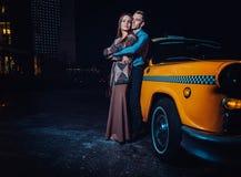 Jeunes couples près de voiture jaune de taxi dans la nuit Photographie stock libre de droits
