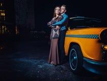 Jeunes couples près de voiture jaune de taxi dans la nuit Photos libres de droits