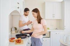 Jeunes couples préparant la nourriture dans la cuisine images stock