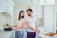 Jeunes couples préparant la nourriture dans la cuisine photos stock