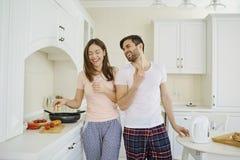 Jeunes couples préparant la nourriture dans la cuisine image libre de droits