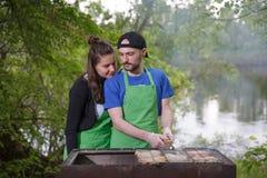 Jeunes couples préparant la viande sur un gril Photo stock