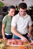 Jeunes couples préparant le déjeuner dans la cuisine Photographie stock libre de droits