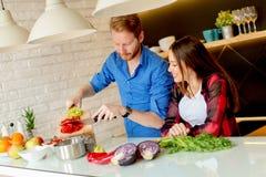 Jeunes couples préparant le repas sain dans la cuisine Photos stock