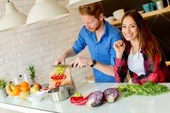 Jeunes couples préparant le repas sain dans la cuisine Images libres de droits