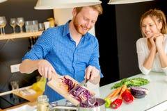 Jeunes couples préparant le repas sain dans la cuisine Photo stock