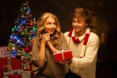 Jeunes couples présentant le cadeau de Noël Photographie stock libre de droits