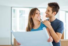Jeunes couples prévoyant leur nouvelle maison photos stock