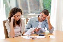 Jeunes couples prévoyant leurs factures domestiques Image stock