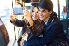 Jeunes couples prenant des selfies avec le smartphone à l'autobus Image libre de droits