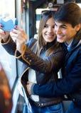 Jeunes couples prenant des selfies avec le smartphone à l'autobus Images stock
