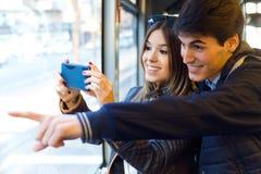 Jeunes couples prenant des selfies avec le smartphone à l'autobus Photo libre de droits