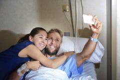 Jeunes couples prenant la photo de selfie à la chambre d'hôpital avec l'homme se situant dans le lit de clinique Photographie stock libre de droits