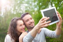 Jeunes couples prenant la photo de selfie au parc Image libre de droits