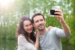 Jeunes couples prenant la photo de selfie au parc Image stock