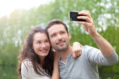 Jeunes couples prenant la photo de selfie au parc Images stock