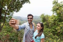 Jeunes couples prenant la photo de Selfie au téléphone intelligent de cellules au-dessus du beau sourire heureux de paysage, d'ho Image stock