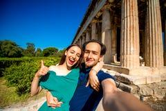 Jeunes couples prenant la photo de selfie avec le temple de Hephaistos sur le fond en agora près de l'Acropole Image libre de droits