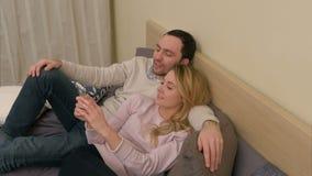 Jeunes couples prenant la photo de selfie utilisant le téléphone portable, se trouvant sur le lit dans la chambre à coucher à la  clips vidéos