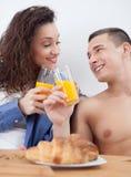 Jeunes couples prenant le petit déjeuner dans le pain grillé de lit avec le jus d'orange Photographie stock