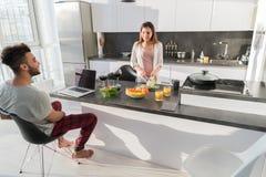 Jeunes couples prenant le petit déjeuner, homme hispanique de femme asiatique faisant cuire la cuisine de nourriture Image stock