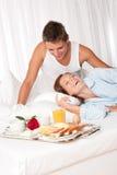 Jeunes couples prenant le petit déjeuner de luxe dans la chambre d'hôtel Photos stock