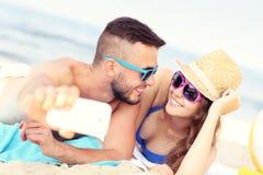 Jeunes couples prenant le selfie à la plage Photographie stock
